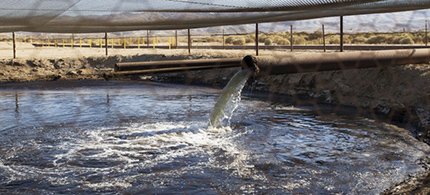 A pipe pours fracking waste into an unlined holding pond in Kern County, California. (photo: Faces of Fracking/Flickr)