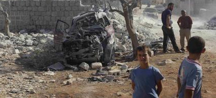 Boys stand near the site of a US airstrike in Syria. (photo: Getty)