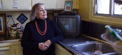 Lydia Smith stands in the kitchen of her home in the Westlake neighborhood of Los Angeles. She has lived in this apartment for 46 years, and now that she is on a fixed income, she pays rent with the aid of Section 8 tenant-based assistance. (photo: Megan Miller/NPR)
