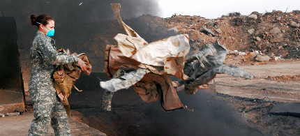 Senior Airman Frances Gavalis tosses unserviceable uniform items into a burn pit at Balad Air Base, Iraq, in 2008. The military destroyed uniforms, equipment and other materials in huge burn pits in Iraq and Afghanistan. Some veterans say those pits are responsible for respiratory problems they are now experiencing. (photo: Senior Airman Julianne Showalter/USAF)