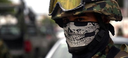 A masked Mexican soldier patrols the streets of Veracruz. (photo: AFP)