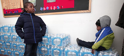Justin Roberson (left), age 6, and Mychal Adams, age 1, wait on a stack of bottled water at a rally where the Rev. Jesse Jackson was speaking about about the water crisis in Flint, Michigan, Jan. 17, 2016. (photo: Bill Pugliano/Getty Images)