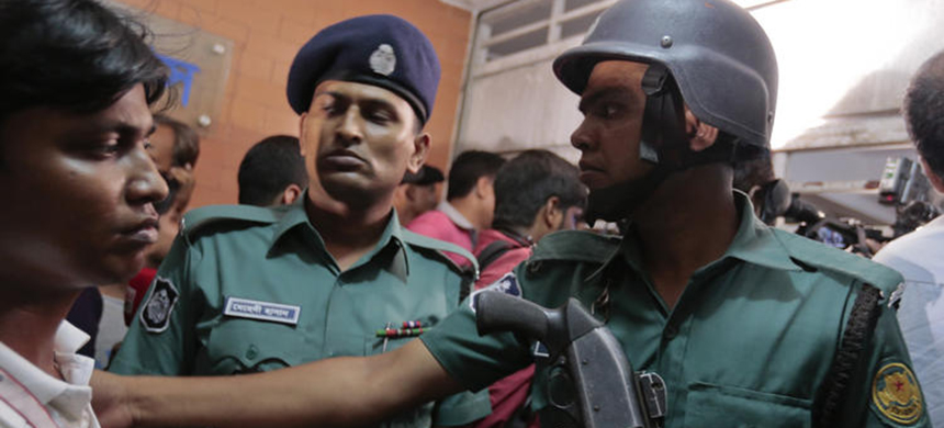 Bangladeshi policemen try to control the crowd of onlookers at a building where two people were found stabbed to death in Dhaka, Bangladesh, on Monday. (photo: A.M. Ahad/AP)