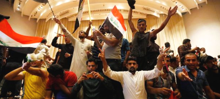 Shia protesters unfurled banners after storming the Iraqi Parliament building. (photo: Reuters)