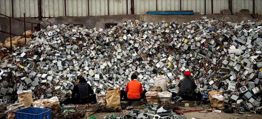 People in front of a pile of e-waste. (photo: Discard Studies)