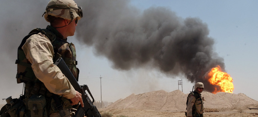 A U.S. soldier stands guard duty near a burning oil well in the Rumaila oil field, 2 April 2003. (photo: Photographer's Mate 1st Class Arlo K. Abrahamson/US Navy)