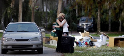 Denise Brunal-Hicks, left, hugs her daughter Samantha, 18, as they stand next to a curb piled with their belongings. Brunal-Hicks was being evicted from her foreclosed home after spending thirteen years at the residence. (photo: Greg Kahn/Naples News)