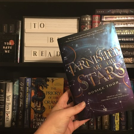 Finished copy of Tarnished Are The Stars held up in front of a bookcase and a TBR sign