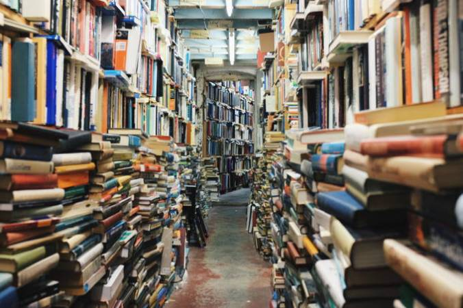 Pictured: aisle between huge stacks and crowded overflowing shelves of books. Which literature to read first?