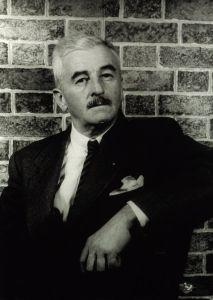 Photo of William Faulkner posing against a brick wall, by Carl Van Vechten