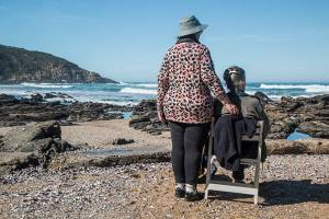 "Two older women at the right foreground are facing a beach with their backs to the camera. One sits in a chair and the other stands to her side with her hand resting on the chair back. ""Chair"" and ""women"" are concrete terms; ""friendship"" is an abstract word."