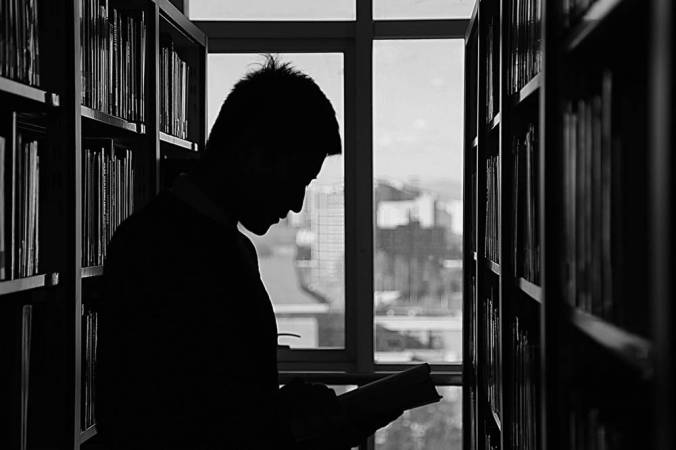 B & W Photo of man in silhouette, in stacks of library, holding an open book.