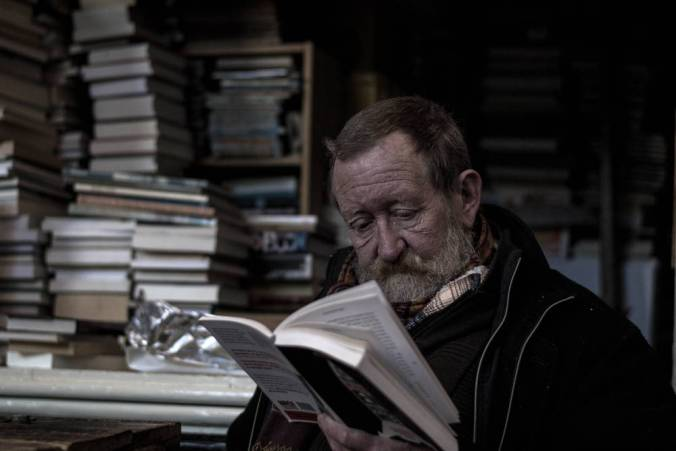 Older man seated reading a book, with stacks of books behind him.