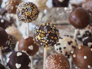 Variety of chocolate sweets on sticks closely compacted.