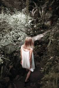 Girl in white shift dress with back to camera walking toward a woodland stream.