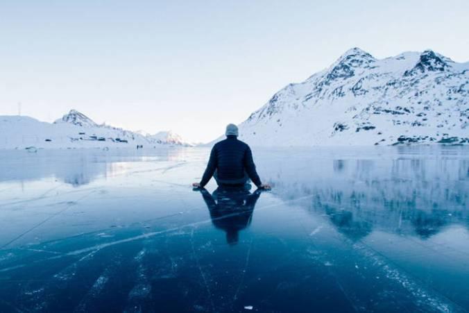 Man sitting on frozen lake facing hill of snow.