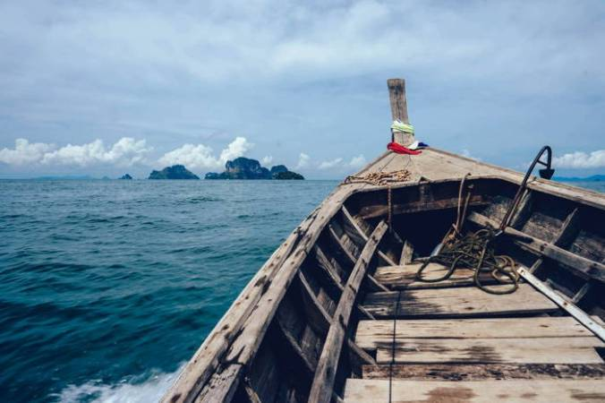 Tip of rowboat pointed toward island in the sea.