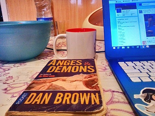 Photo shows paperback copy of Angels and Demons by Dan Brown, lying on table next to laptop in front of coffee mug.