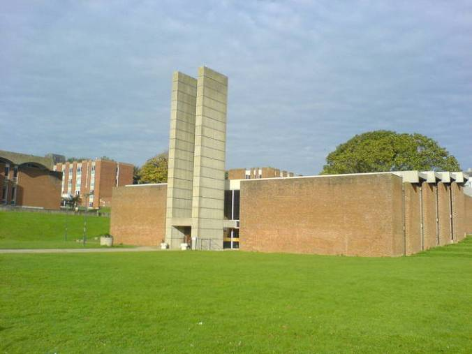 Photo of Univ. of Sussex Lecture Hall, modern architecture: plain, flat, square orange brick building with double stack of concrete blocks at entrance.