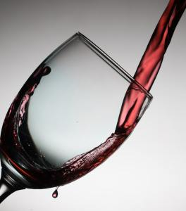 Photo shows stream of red wine being poured into a tipped glass.