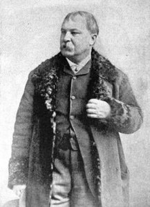 1887 Photograph of stocky man with handlebar mustache, wearing a buttoned vest and a long overcoat with a fur collar.