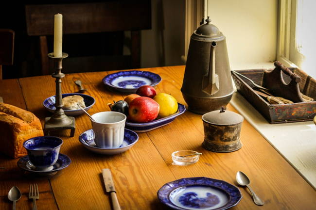Still life photo showing rough wooden table, old-fashioned metal coffee pot, tableware, and blue and white dishes with fruit in bowl.