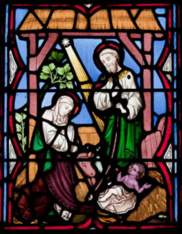 Muticolored stained glass window shows baby Jesus in manger, bottome right, with mother Mary kneeling on left and father Joseph standing looking at baby, on the left.