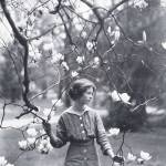 B & W photo of slender young woman in 1920s dress beneath blooming branches.