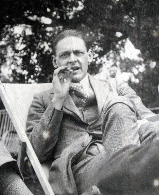 B & W Photo of T. S. Eliot smoking cigar in beach-style chair, wearing three-piece suit.
