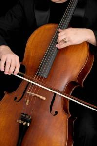 Close-up photo of a cello showing bow and hands of the player.