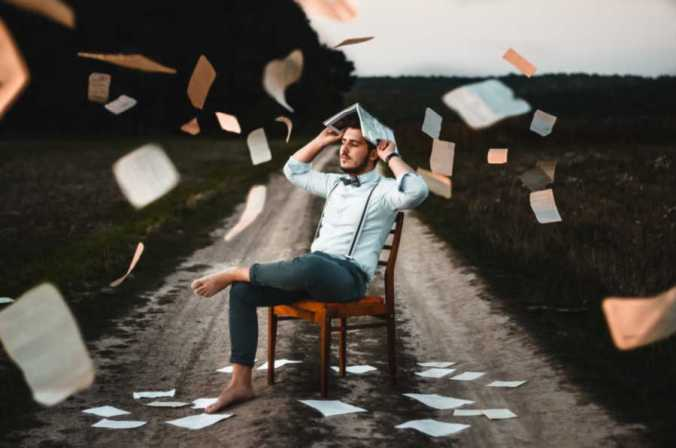Barefoot young man wearing suspenders sits in wooden chair in middle of dirt road with book open on his head and book pages flying around him in the air. Characterization techniques help characters spring from pages as if real.