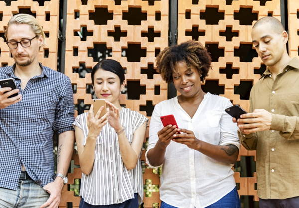 Two men and two women stand shoulder to shoulder using Smartphones. They just might be chatting on social media about classic literature.