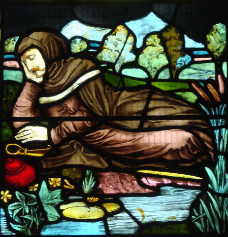 Beautiful stained glass in shades of brown and blue depicting author William Langland, reclining in contemplation near a brook.