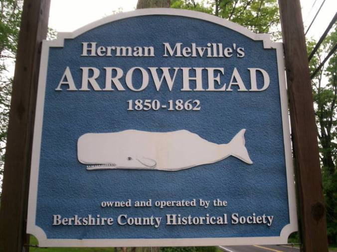 Bright blue sign with a white whale announcing the location of the Melville Arrowhead Farm.
