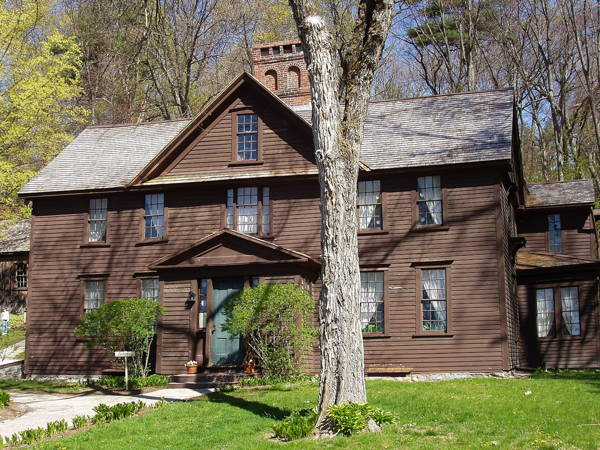 Large rambling two-story brown wood-sided farmhouse shows the rough but charming environment Alcott lived in.