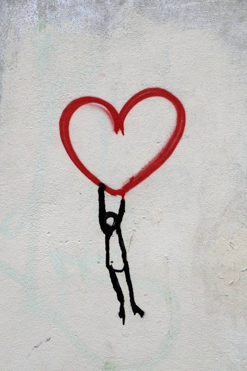 Art piece: Stick figure clings to large red heart.