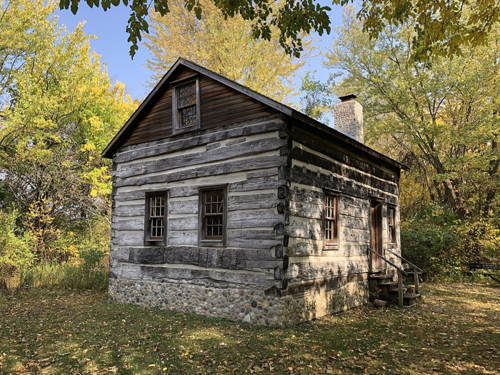 Solitary log cabin in woods.