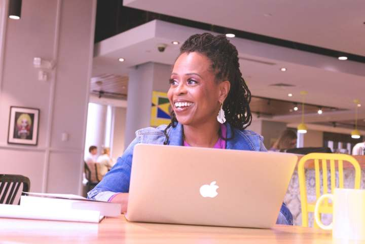 Black woman, author Alicia D. Williams works on a laptop in a cafe
