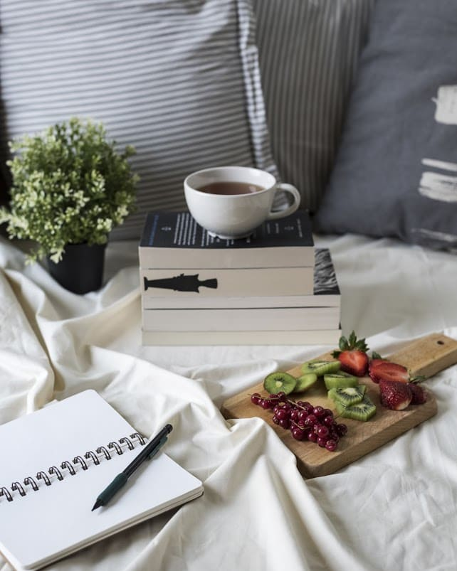 A stack of books lie on a bed with a fruit board to the side and a cup of tea on the stacks