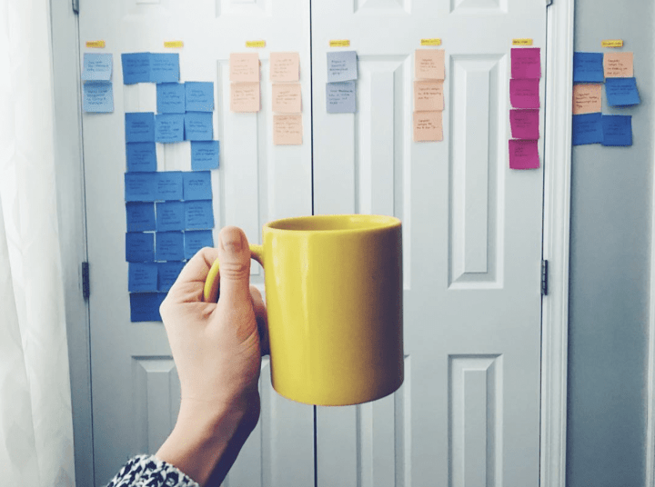a mug held up against post-it notes on a door