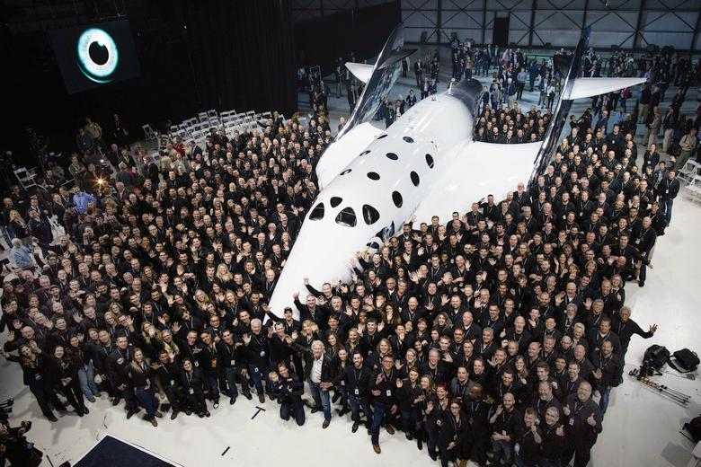 Virgin Galactic and The Spaceship Company team pose for photographer in Mojave, CA. Virgin Spaceship Unity is unveiled in Mojave, California, Friday February 19th, 2016. VSS Unity is the first vehicle to be manufactured by The Spaceship Company, Virgin Galactic's wholly owned manufacturing arm, and is the second vehicle of its design ever constructed. VSS Unity was unveiled in FAITH (Final Assembly Integration Test Hangar), the Mojave-based home of manufacturing and testing for Virgin Galactic's human space flight program. VSS Unity featured a new silver and white livery and was guided into position by one of the company's support Range Rovers, provided by its exclusive automotive partner Jaguar Land Rover.