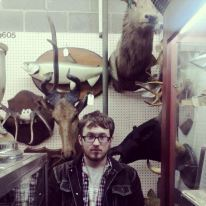 A photo of Justin Carter wearing glasses and a denim jacket. He has brown hair and is standing in front of taxidermy.