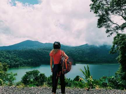 A girl exploring Bali's mountains, lake Buyan, a backpacker with a helmet from her scooter.