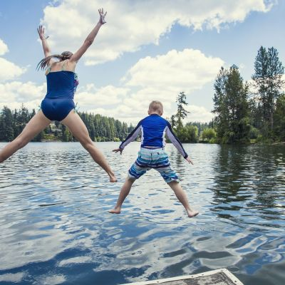 Kids jumping into lake on a summer vacation