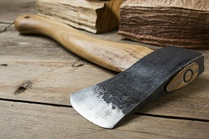 Wooden handle axe lying on wooden table, ready for use