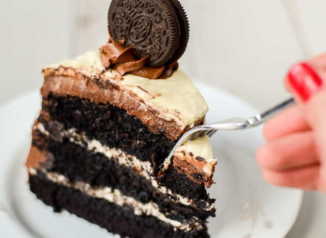 This Oreo Layer Cake combines super fudgy cake, cream cheese filling with crushed Oreo, thick chocolate frosting, and white chocolate glaze, all in one decadent dessert.