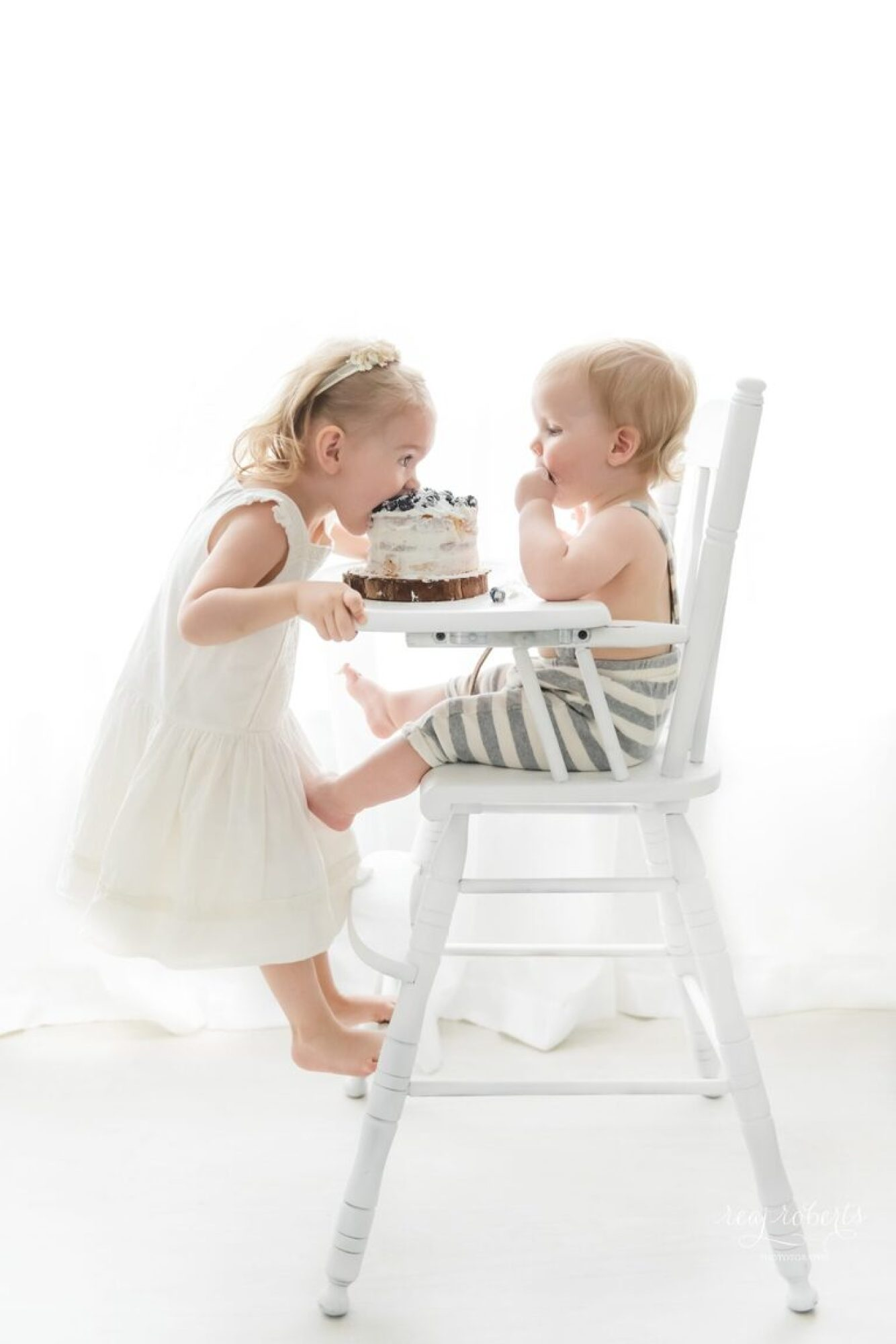 baby in high chair cake smash with big sister taking a bite | Reaj Roberts Photography
