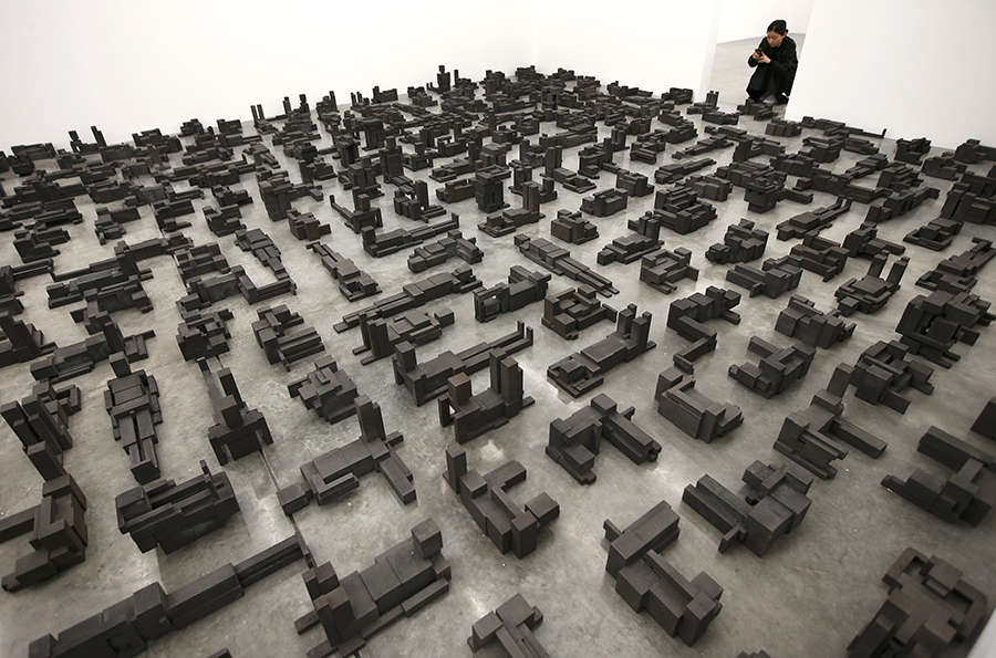 "A member of the gallery takes a photograph of a piece called ""Sleeping Field"", by artist Antony Gormley, which forms part of an exhibition entitled ""Fit"", at the White Cube gallery in London, Britain September 29, 2016.   REUTERS/Peter Nicholls"