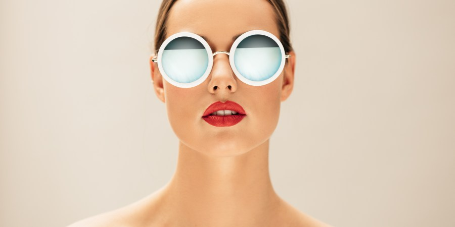Woman wearing a cute pair of sunglasses, she probably didn't save money on glasses by buying them online though. Sad face.