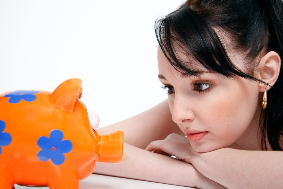 Girl staring at her piggy bank waiting for her emergency fund to grow